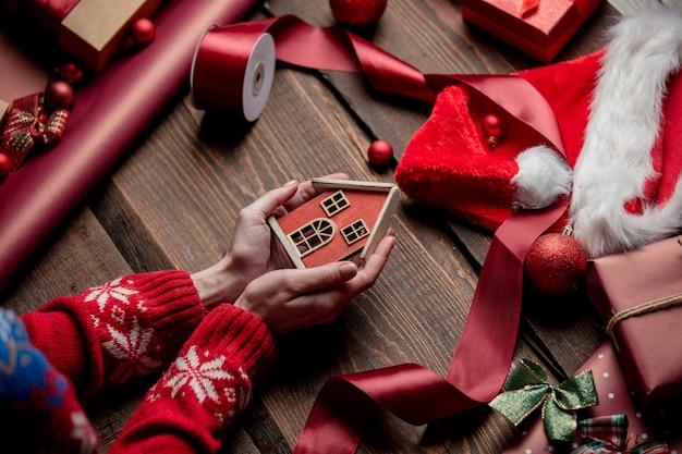 Mulher com as mãos segurando uma casa de brinquedo na mesa de madeira na hora do embrulho Foto Premium