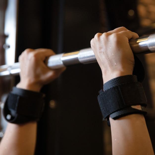 Mulher com as mãos suadas fazendo exercícios na barra horizontal no ginásio Foto Premium