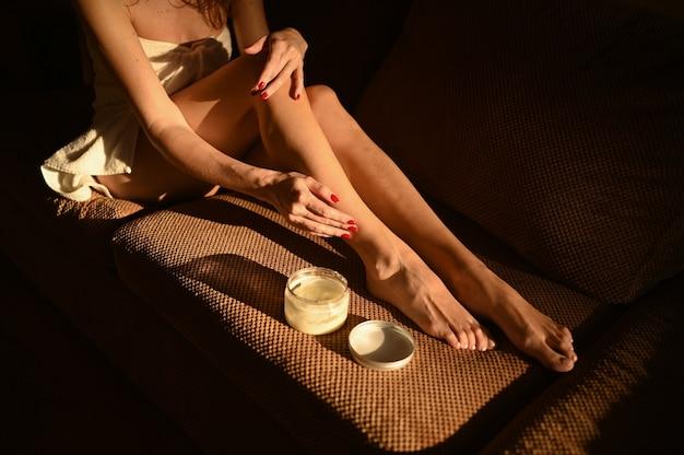 Mulher com as pernas nuas sentada no sofá em casa em um dia ensolarado Foto Premium