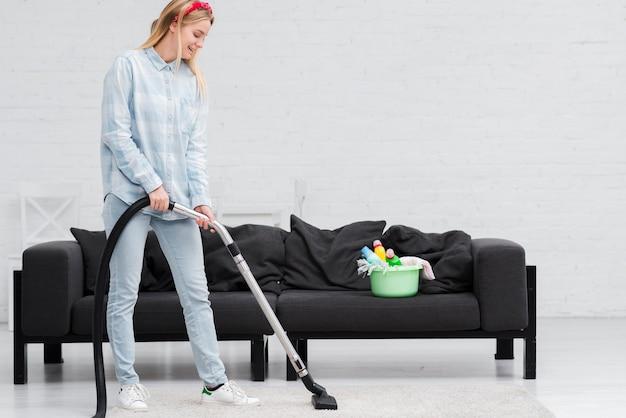 Mulher com aspirador de pó em casa Foto gratuita