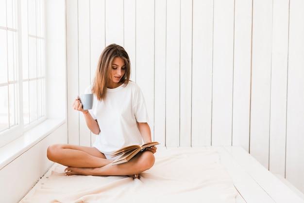 Mulher, com, assalte, leitura, livro, branco, superfície Foto gratuita
