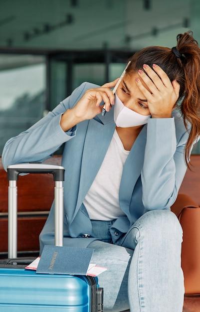 Mulher com bagagem no aeroporto falando ao telefone durante a pandemia Foto Premium