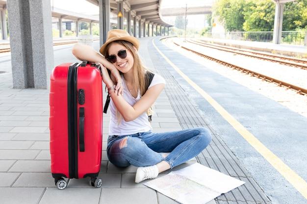 Mulher, com, bagagem, sentar chão Foto Premium