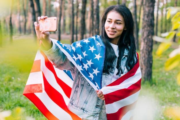 Mulher, com, bandeira, levando, selfie Foto gratuita