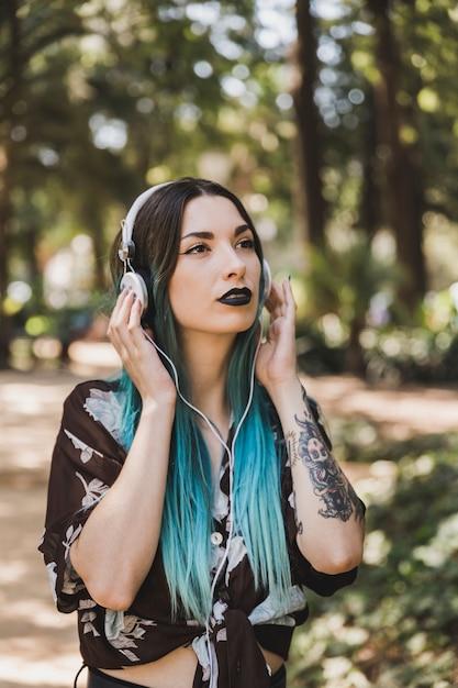 Mulher com batom preto ouvindo música no fone de ouvido no parque Foto gratuita