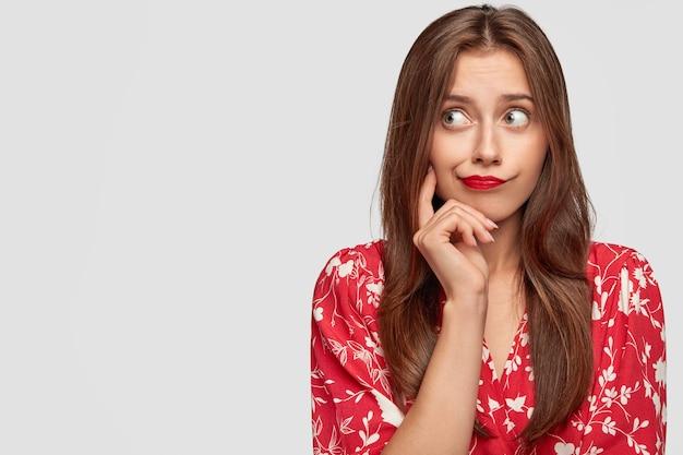 Mulher com batom vermelho posando contra a parede branca Foto gratuita
