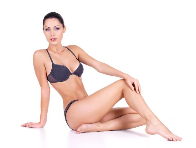 Mulher com belas pernas longas e finas de biquíni sentada no fundo branco Foto gratuita