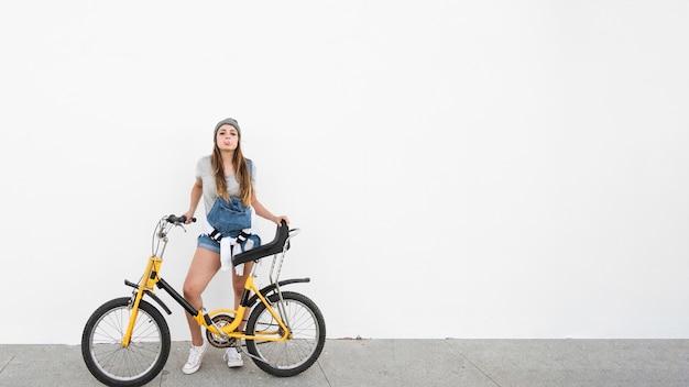 Mulher, com, bicicleta, soprando, pastilha elástica, ligado, calçada Foto gratuita