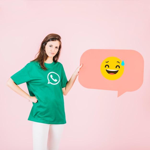 Mulher, com, bolha fala, mostrando, face sorridente, e, suor frio, emoji Foto gratuita