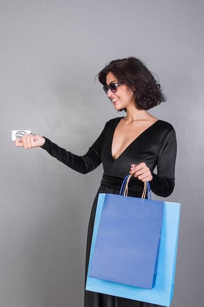 Mulher, com, bolsas para compras, dar, cartão crédito Foto gratuita