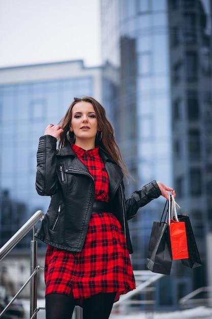 Mulher, com, bolsas para compras, por, centro comercial, exterior, em, inverno Foto gratuita