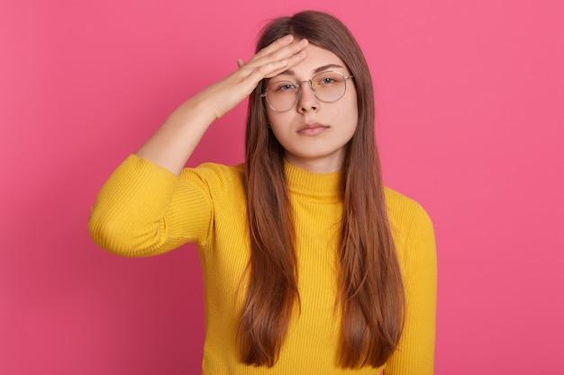 Mulher com cabelo comprido e bonito sofrendo de dor de cabeça terrível, com expressão chateada, mantendo as mãos na testa Foto gratuita
