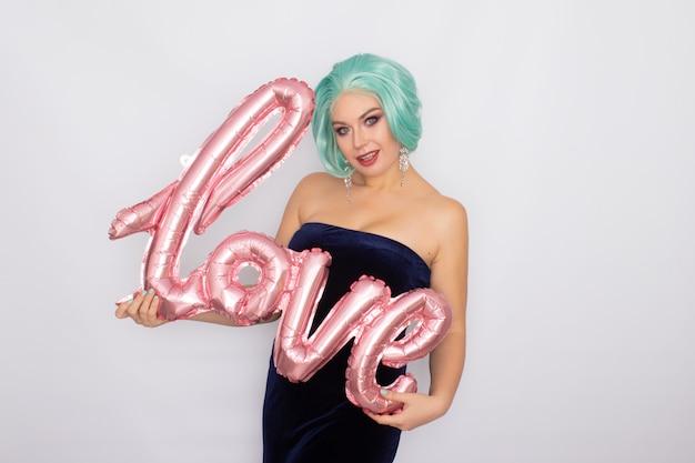 Mulher com cabelo curto de menta no vestido de veludo azul escuro, segurando o balão com a palavra amor Foto Premium