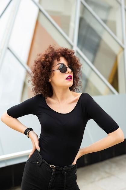Mulher com cabelo encaracolado posando Foto gratuita