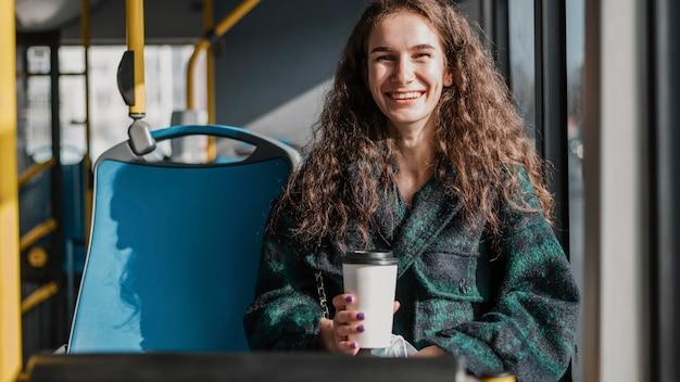 Mulher com cabelo encaracolado segurando um café no ônibus Foto gratuita