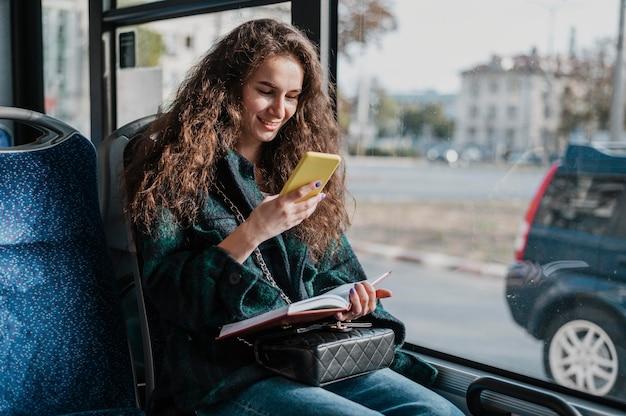 Mulher com cabelo encaracolado viajando de ônibus Foto gratuita