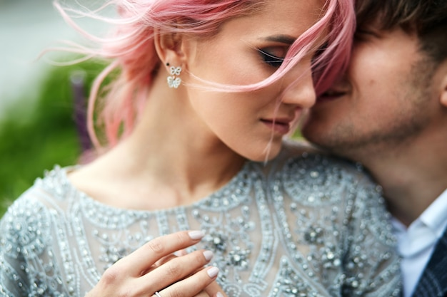 Mulher com cabelo rosa se inclina para o homem dela. Foto gratuita