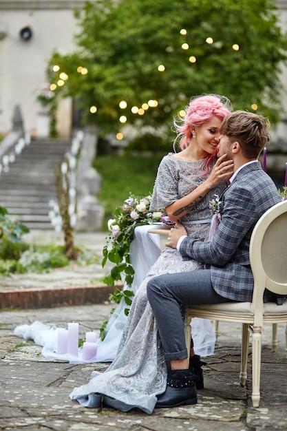 Mulher com cabelo rosa senta-se nos joelhos do homem na mesa de jantar em um quintal Foto gratuita