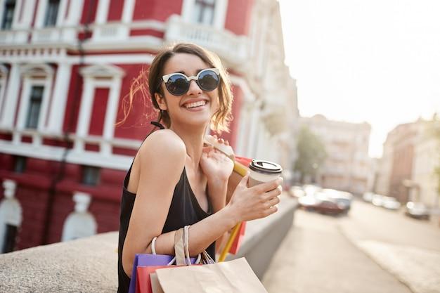 Mulher com cabelos escuros em óculos de sol e vestido preto, sorrindo brilhantemente Foto gratuita