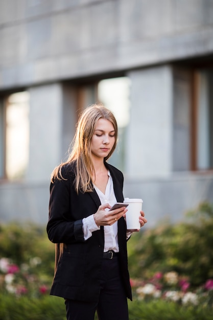 Mulher, com, café, e, telefone, tiro mid Foto gratuita