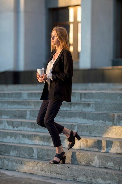 Mulher, com, café, ir baixo Foto gratuita