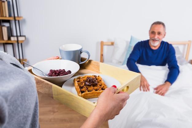 Mulher, com, café manhã, perto, envelhecido, homem sorridente, em, duvet, cama Foto gratuita