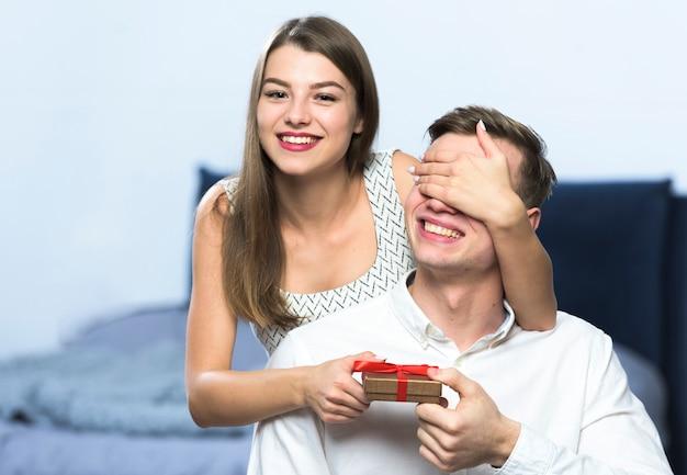 Mulher com caixa de presente, cobrindo os olhos do homem Foto gratuita