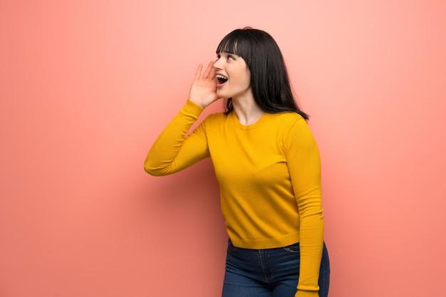 Mulher com camisola amarela sobre parede rosa gritando com a boca aberta para o lateral Foto Premium