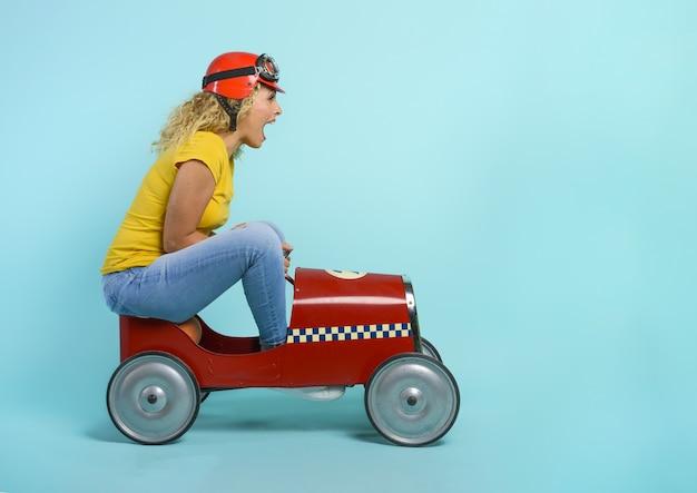 Mulher com capacete vermelho dirige um carro de brinquedo rápido. fundo ciano. Foto Premium