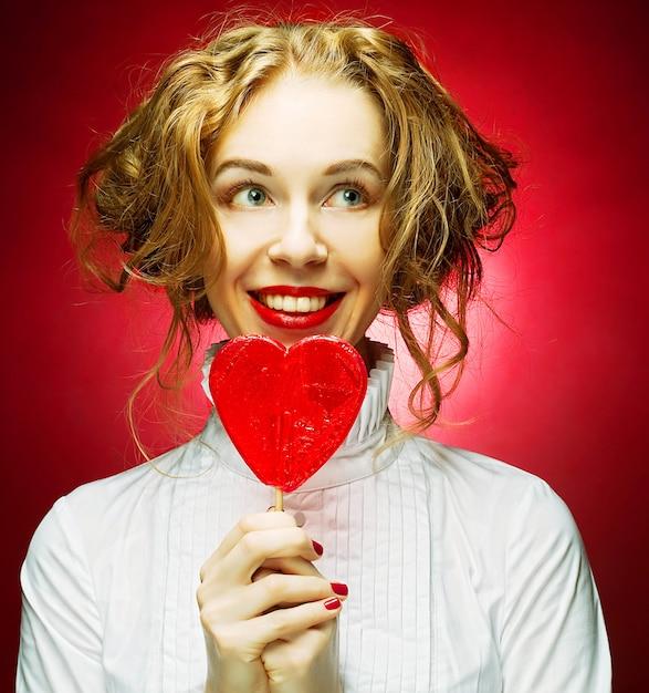 Mulher com caramelo de coração sobre fundo vermelho Foto Premium