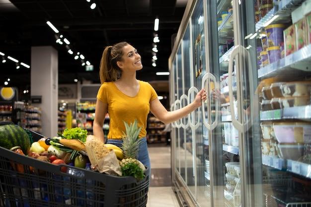 Mulher com carrinho de compras tirando comida congelada da geladeira no supermercado Foto gratuita