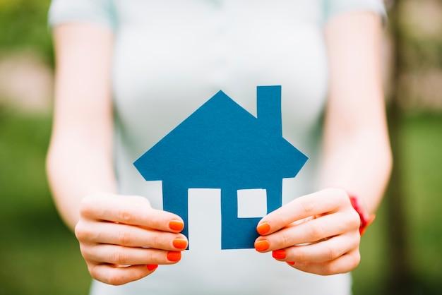 Mulher com casa azul recortada Foto gratuita