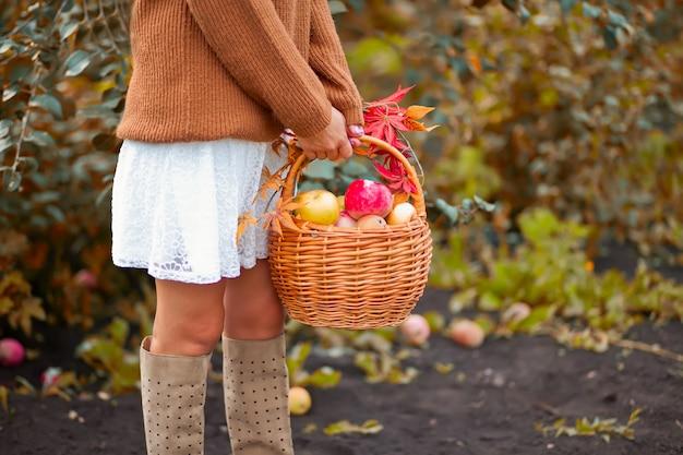 Mulher com cesto cheio de maçãs maduras em um jardim Foto Premium