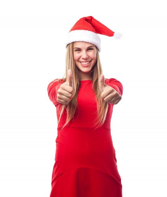 Mulher com chapéu de papai noel mostra os polegares acima Foto gratuita