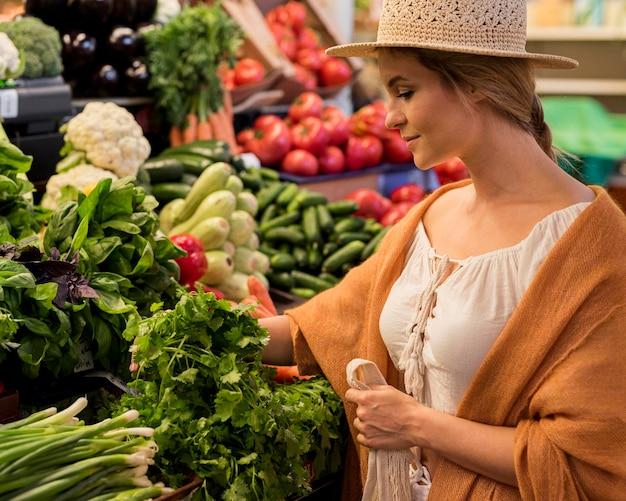 Mulher com chapéu de sol no mercado, vista lateral Foto gratuita