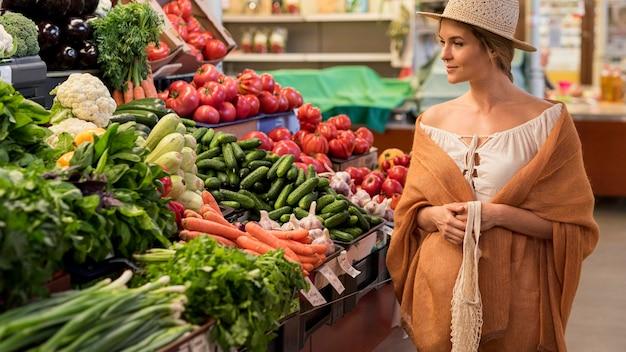 Mulher com chapéu de sol olhando para vegetais Foto Premium