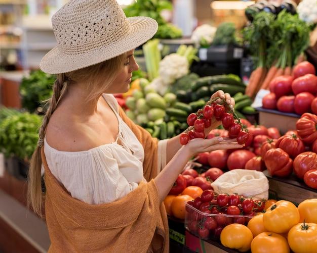 Mulher com chapéu de sol segurando tomate cereja Foto gratuita