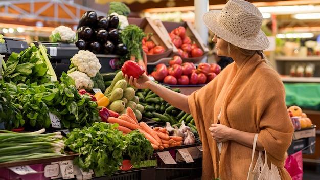 Mulher com chapéu de verão comprando pimentão Foto Premium