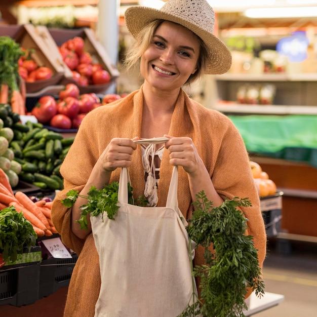 Mulher com chapéu de verão na mercearia sorrindo Foto gratuita