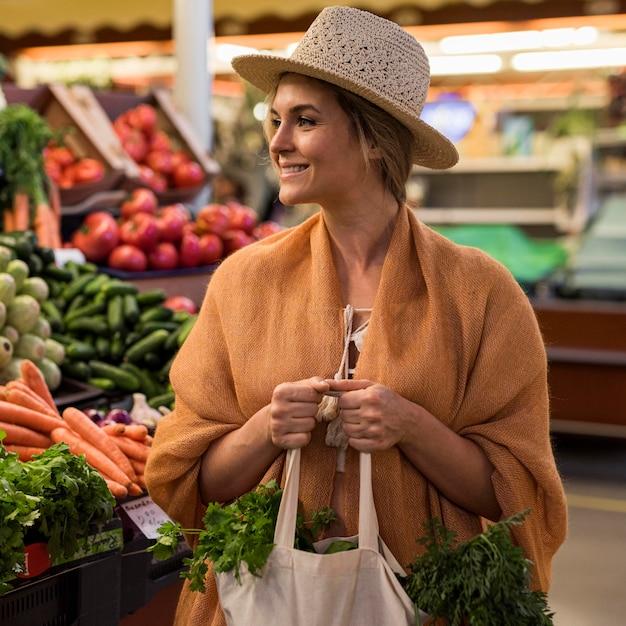 Mulher com chapéu de verão no mercado Foto gratuita