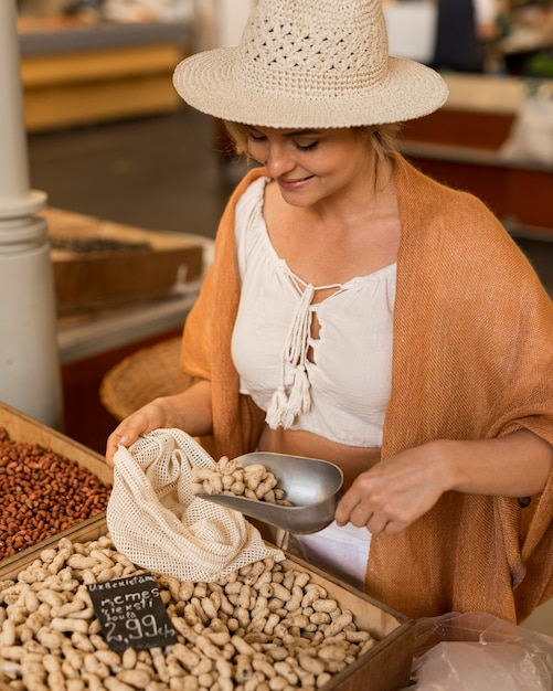 Mulher com chapéu levando comida seca no mercado Foto gratuita