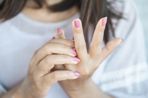 Mulher com coceira e coçar a mão Foto Premium