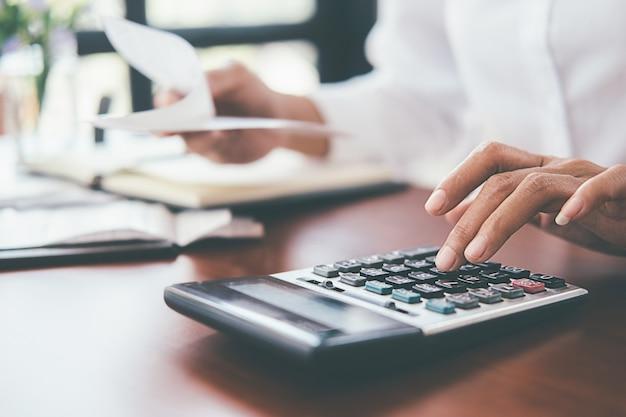 Mulher com contas e calculadora. mulher que usa a calculadora para calcular contas na tabela no escritório. Foto Premium