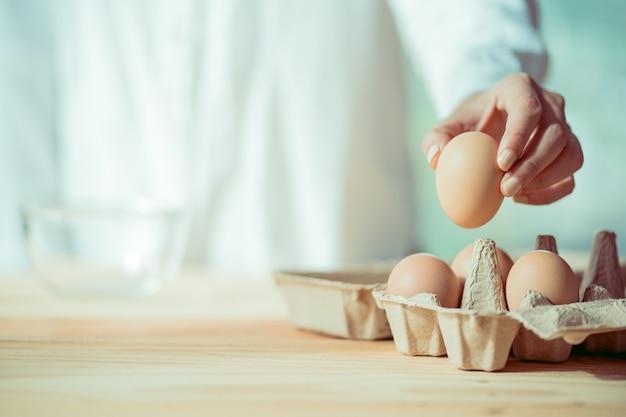 Mulher com creme de unha polida pegar ovo da bandeja de papel, aconchegante estilo de cozinha Foto Premium