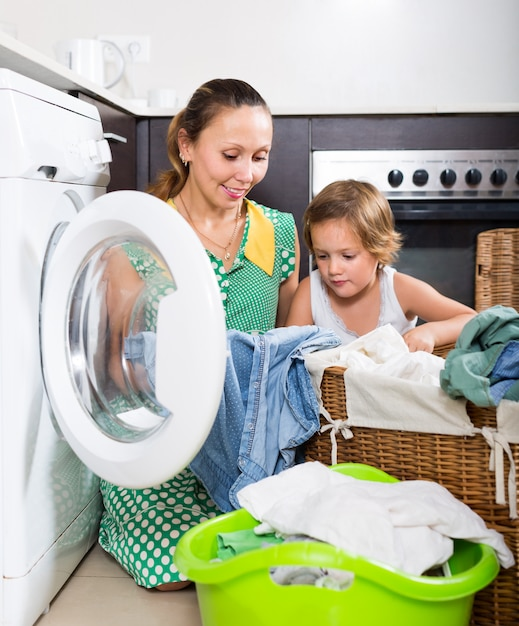 Mulher com criança perto da máquina de lavar Foto gratuita