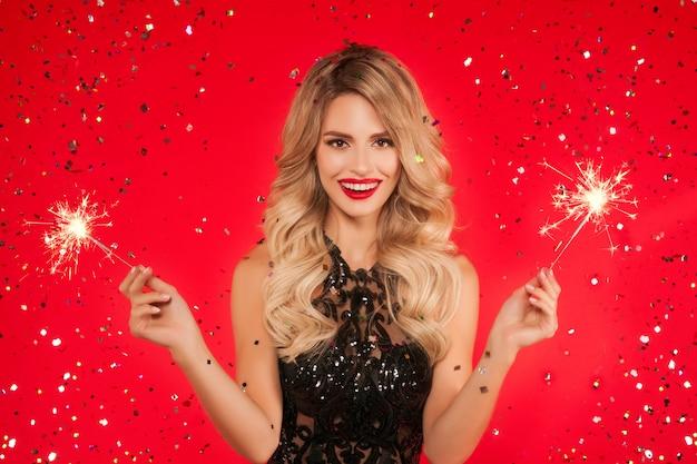 Mulher com diamante celebrando a festa de ano novo. retrato de menina sorridente linda num vestido preto brilhante, jogando confete Foto Premium