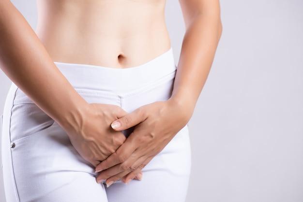 Mulher com dor de estômago dolorosa com as mãos segurando pressionando a virilha inferior do abdômen Foto Premium