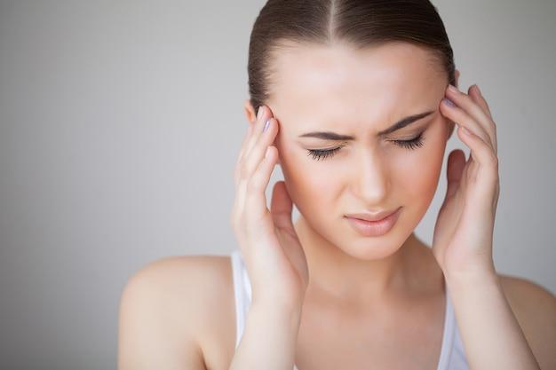 Mulher com dor sentindo mau e doente, tendo dor de cabeça e febre, segurando a mão na testa. menina cansado infeliz bonita que sofre da dor e do esforço principais dolorosos. cuidados de saúde. alta resolução Foto Premium