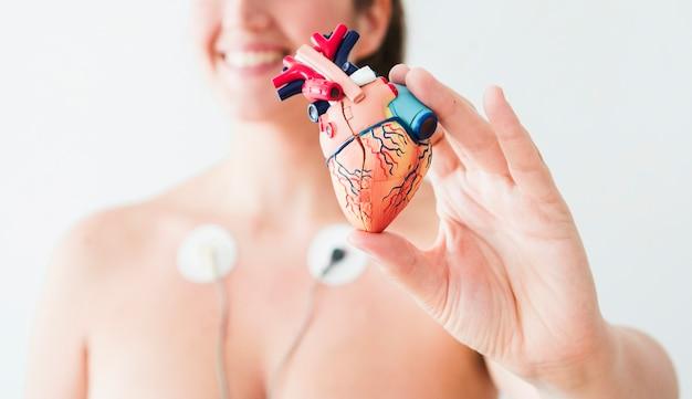 Mulher, com, eletrodos, segurando, estatueta, de, coração Foto gratuita