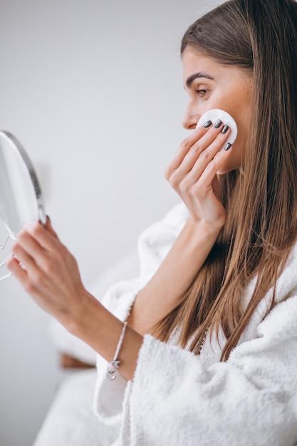 Mulher, com, espelho, removendo, maquilagem, com, almofada Foto gratuita